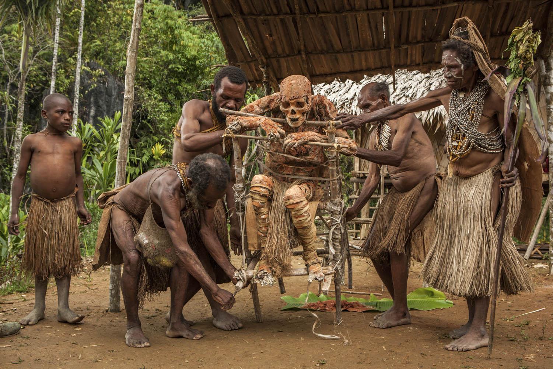 PNG08_0612_4936_1Mumie Moymango wird von seinen Familienangehörigen, darunter auch Sohn Gemtasu, restauriert, Papua Neuguinea.Mummified Moymango gets restored by his son Gemtasu, Papua New Guinea.