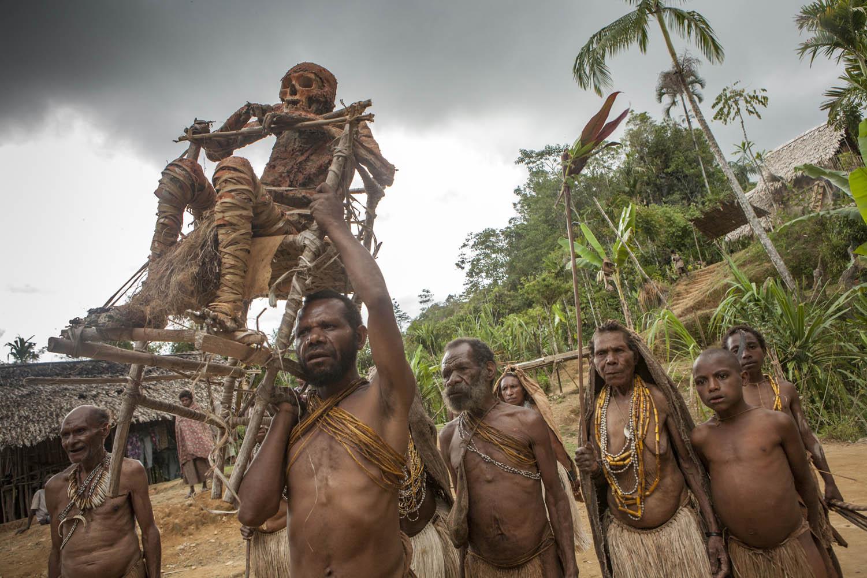PNG08_0612_4971Die restaurierte Mumie Moymango wird mit einer Zeremonie zurück zum Felsvorsprung über dem Dorf getragen, Papua Neuguinea.The restored mummy Moymango gets carried back to the rock ledge above the village, Papua New Guinea.