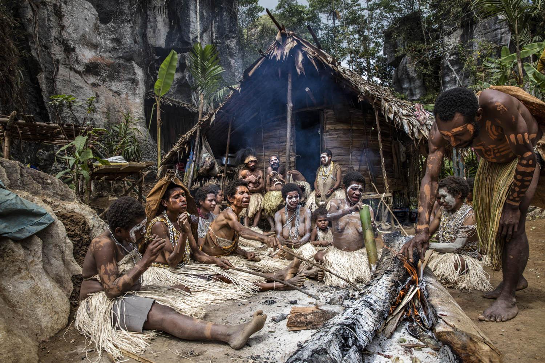 150813_09785Gemtasu's Familie sitzt vor der Räucherhütte, in der ihr Familienoberhaupt mumifiziert wird, Papua Neuguinea.Gemtasu's family in front of the smoking hut, where Gemtasu is getting mummified, Papua New Guinea.