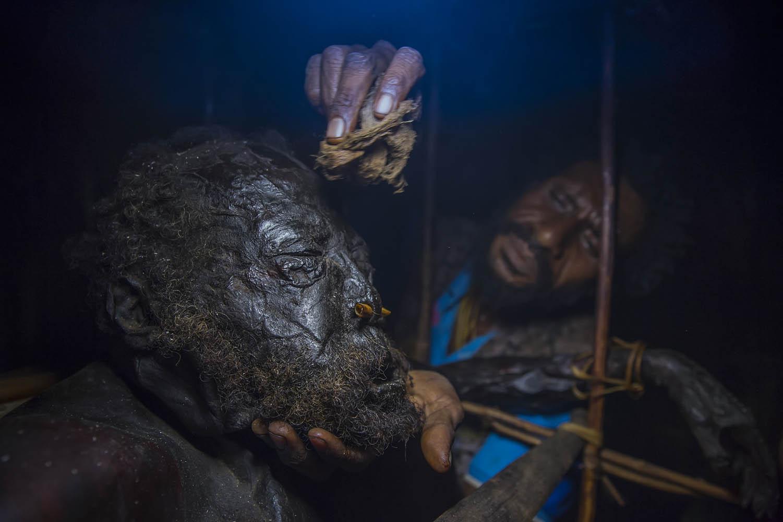 150813_09389Andrew wischt Gemtasu den Leichensaft von der Stirn, Papua Neuguinea.Andrew wipes the body juices from Gemtasu's face, Papua New Guinea.